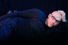 Man Lying. Man in black lying on the floor. Studio-style portrait Stock Photo
