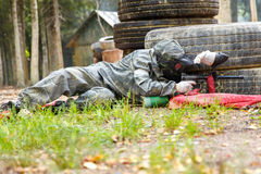 Man lying in ambush with paintball marker Stock Photography