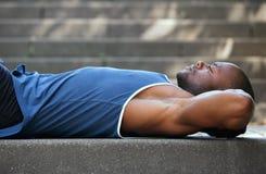 Man lying on back resting outside Stock Photos