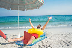 Man lying on the beach with flippers and rubber ring Royalty Free Stock Image