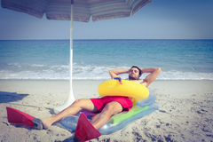 Man lying on the beach with flippers and rubber ring Stock Images