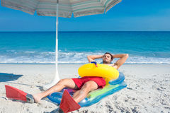 Man lying on the beach with flippers and rubber ring Stock Photos