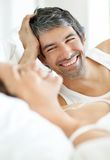 Man lying on bed besides his wife Stock Images