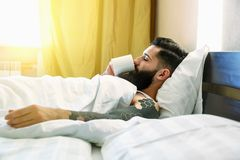 Man lying in bed and drinking coffee Stock Photography