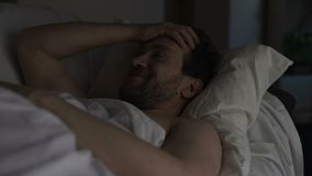 Man lying in bed, having some pleasant thoughts and smiling, nostalgic memories