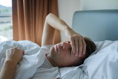 Man lying in bed at home suffering from headache or hangover. Caucasian man lying in bed at home suffering from headache or hangover. Concept of problem with Royalty Free Stock Image