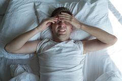Man lying in bed at home suffering from headache or hangover. Caucasian man lying in bed at home suffering from headache or hangover. Concept of problem with Stock Image