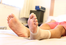 Man lying on the bed with Injured ankle Royalty Free Stock Photography