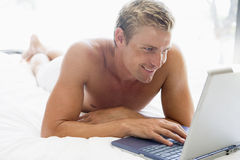 Man lying in bed with laptop Royalty Free Stock Photos