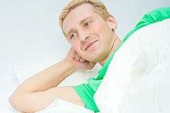 Man lying in bed laughing Royalty Free Stock Photography