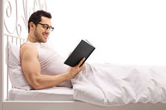 Man lying in bed and reading a book Royalty Free Stock Images