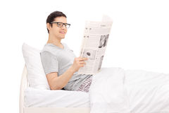 Man lying in bed and reading a newspaper Stock Images