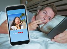 Man lying on bed sending good night kiss text with mobile phone having internet video call with Asian Chinese girlfriend in long Royalty Free Stock Photos