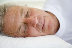 Man lying in bed sleeping Stock Image