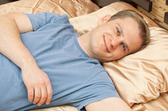 Man lying in bed and smiling. This is a portrait of young man lying in bed and smiling stock photo