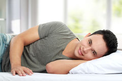 Man lying in bed smiling Stock Photography