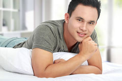 Man lying in bed smiling Royalty Free Stock Images