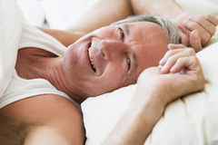 Man lying in bed smiling Stock Images