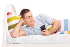 Man lying in bed and surfing on his cell phone Stock Image