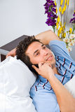 Man lying on bed talking by phone Royalty Free Stock Image