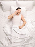 Man lying in bed and talking on phone Royalty Free Stock Image