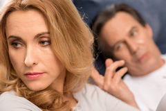 Man lying in bed and touching hair of upset middle aged woman. Close up view men lying in bed and touching hair of upset middle aged woman Stock Images