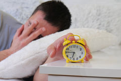 Man lying in bed turning off an alarm clock close up. Hate waking up early. Selective focus image Stock Photo