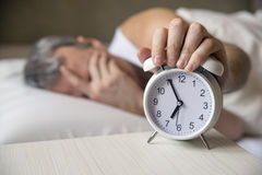 Man lying in bed turning off an alarm clock in the morning at 7am. Attractive man sleeping in his bedroom Royalty Free Stock Photography