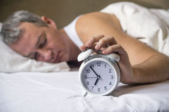 Man lying in bed turning off an alarm clock in the morning at 7a Royalty Free Stock Image
