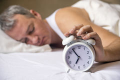 Man lying in bed turning off an alarm clock in the morning at 7a Royalty Free Stock Photos