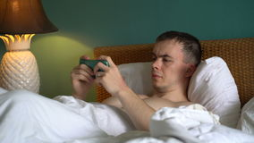 Man is lying in bed and is using the application on his smartphone. stock footage