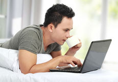Man lying on a bed and using a laptop computer Stock Images