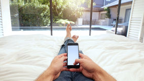Man lying on bed using smart phone Royalty Free Stock Photo