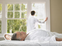 Man Lying In Bed With Woman Standing At Window Stock Photo