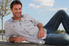 Man lying on a bench Stock Images