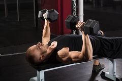 Man Exercising With Dumbbell. Man Lying On Bench Press While Exercising With Dumbbell Stock Image