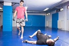 Man lying on blue mats during box training Royalty Free Stock Photo