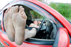 Man lying in car. Man in car legs out of window royalty free stock photo