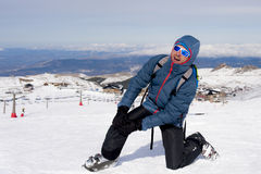 Man lying on cold snow after ski crash holding his injured knee in pain at Sierrna Nevada resort Royalty Free Stock Photography