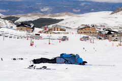 Man lying on cold snow after ski crash at Sierra Nevada resort in Spain with mountains Stock Photos