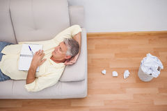 Man lying on couch with crumpled papers Royalty Free Stock Images