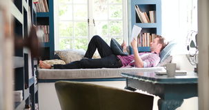 Man Lying On Couch In Home Office Using Digital Tablet. View through doorway of man lying on couch using digital tablet and reading document in home office.Shot stock footage