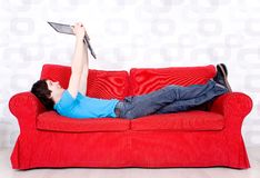 Man lying on couch with laptop Royalty Free Stock Images
