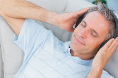 Man lying on couch listening to music with eyes closed. At home royalty free stock photography