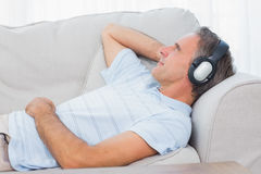 Man lying on couch listening to music Royalty Free Stock Photos