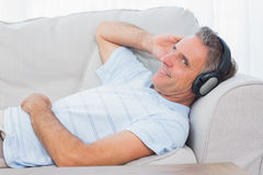 Man lying on couch listening to music smiling at camera Stock Photos