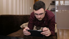 Man lying on the couch listening to music and using tablet at home in the living room stock video footage