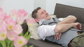 Man lying on couch and looks very happy and satisfied stock footage