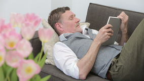 Man lying on couch and is reading a book stock video footage