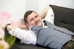 Man lying on couch and smiling Royalty Free Stock Images